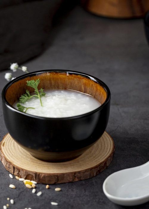 rice-soup-black-bowl-wooden-support-white-spoon
